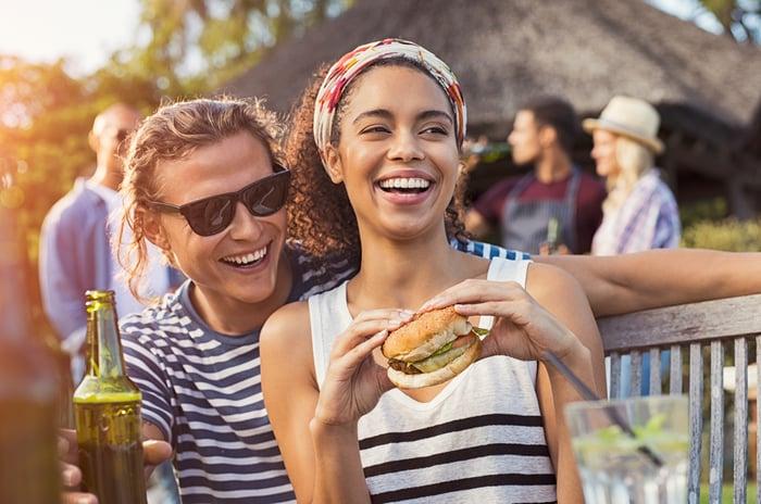 A couple enjoys a veggie burger at a summer barbecue.