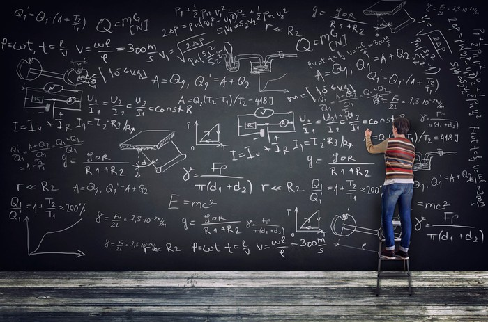 A student fills an oversized blackboard with complicated equations.