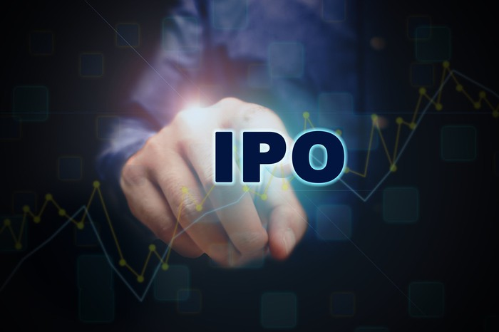 Man's finger pointing to IPO with a stock chart going up in the background
