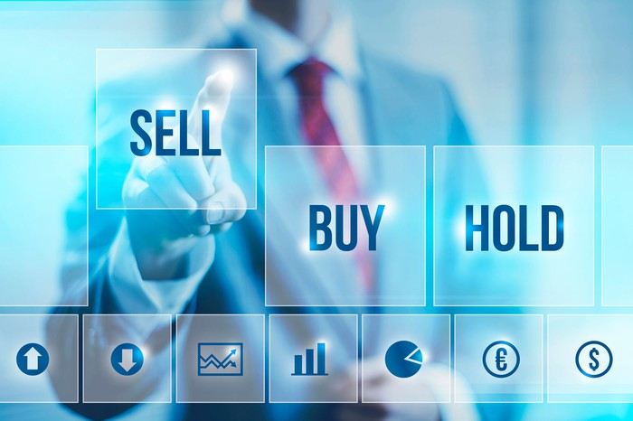 """Businessman pointing to """"sell"""" icon next to """"buy"""" and """"hold"""" icons"""