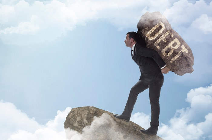 Man in a suit carrying a large rock labeled debt on his back up a mountain