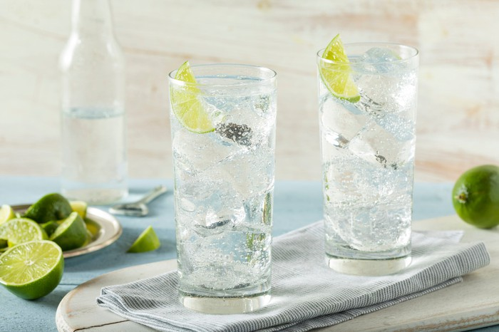 Two glasses of hard seltzer with limes.