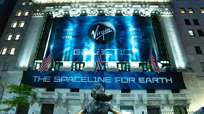 New York Stock Exchange with banner about Virgin Galactic hanging from columns and lit up.