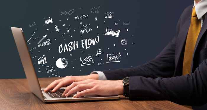 Someone sitting at a laptop in a suit and tie with various charts appearing to come out. The words Cash Flow are in the center.