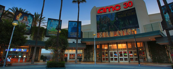 The entrance to an AMC multiplex surrounded by palm trees