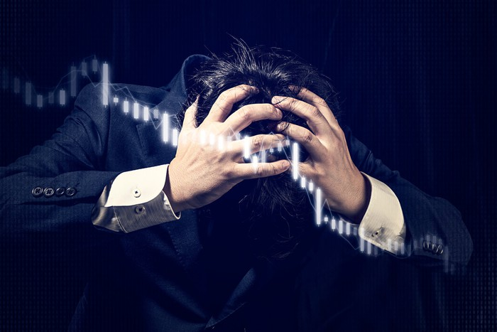 Man in a suit holds his head in panic with an overlay of a declining digital chart display.