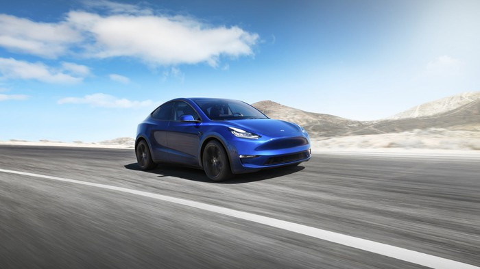 A blue Model Y on a road with hills in the background