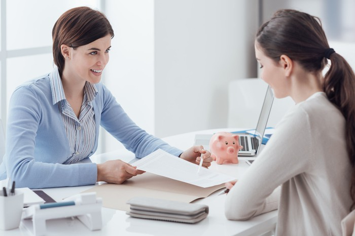 Financial adviser working on a plan with a young woman.