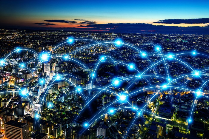 Blue network drawn over a lit-up city at night
