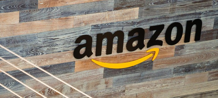 An Amazon logo in the form of a sign on a wall made of wooden planks.