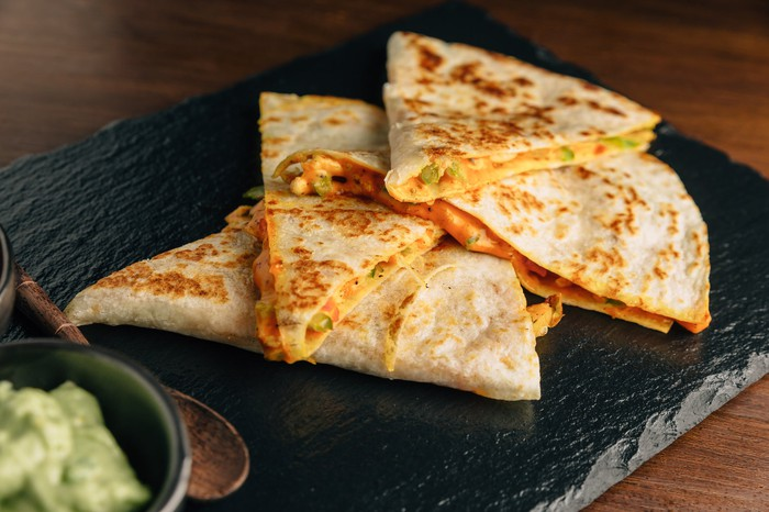 Chicken quesadilla slices served on a black wooden board.