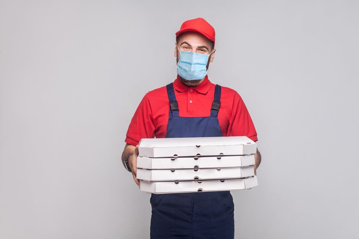 A man wearing a mask as he holds pizza delivery boxes.