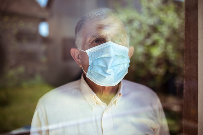 Older man wearing face mask while looking out of a window.
