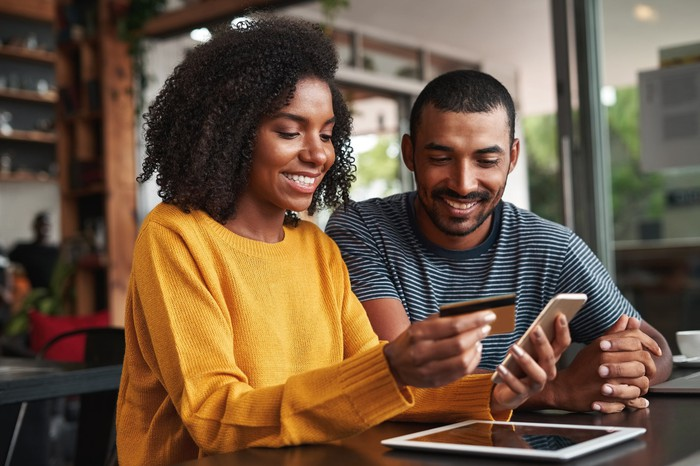 A young couple happily look at a credit  card while holding a smartphone as a tablet lies  on the table next to them.