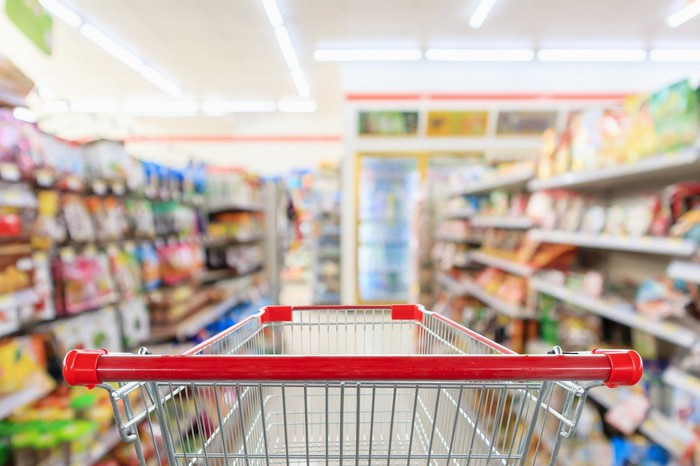 An empty grocery cart heading into a loaded supermarket aisle.