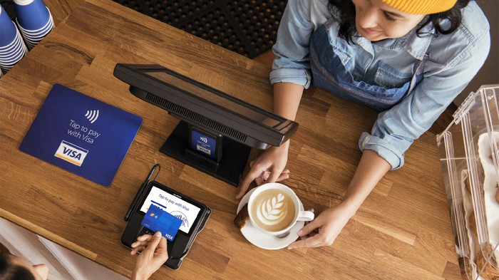 Overhead view of a person buying coffee at a cafe with a Visa card.