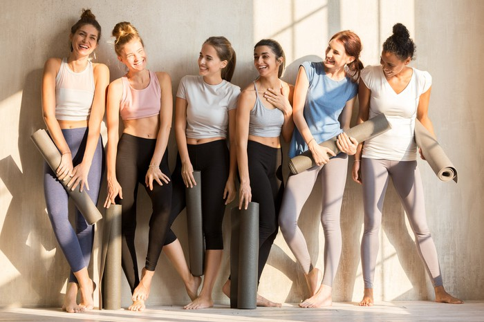 A group of young women laugh together as they wait for yoga class to start.