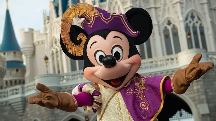 Mickey Mouse in regal attire in front of Florida's Magic Kingdom castle.
