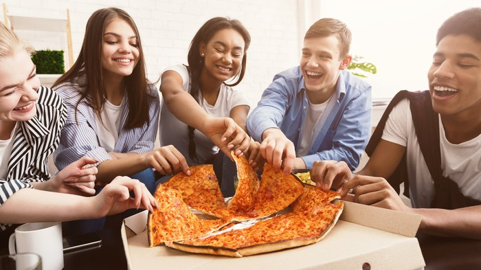 Five young adults sharing a delivered pizza.