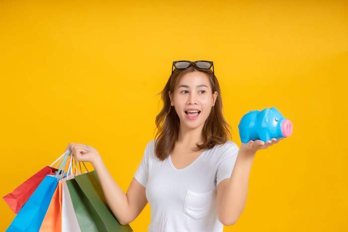 A woman with shopping bags in her right hand and a piggy bank in her left hand.