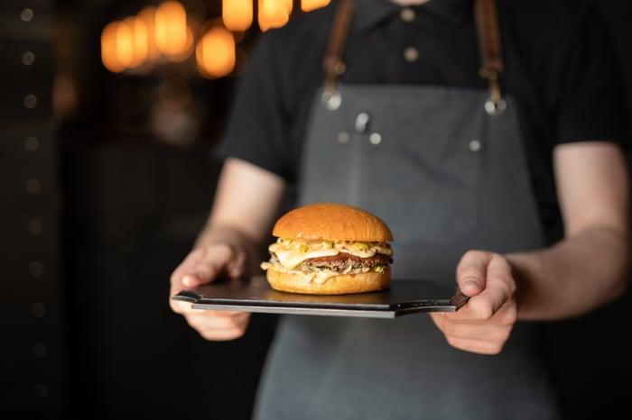 Waiter serving a hamburger
