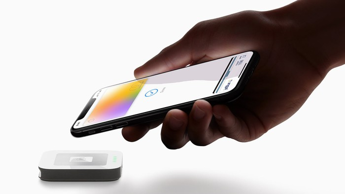 A hand holding an iPhone paying with the Apple card using Apple Pay.