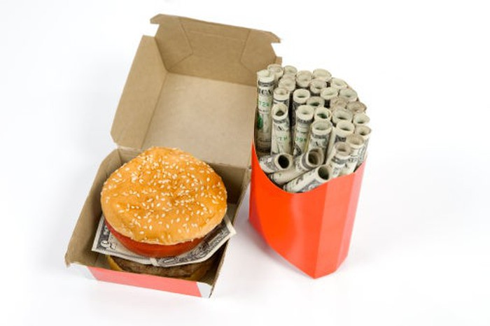 A burger with a five-dollar bill instead of lettuce in a cardboard carton next to a paper French fry box stuffed with tightly rolled dollar bills.
