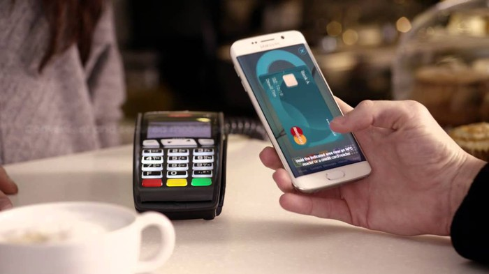 Mastercard on phone being used to pay for goods at a cafe.