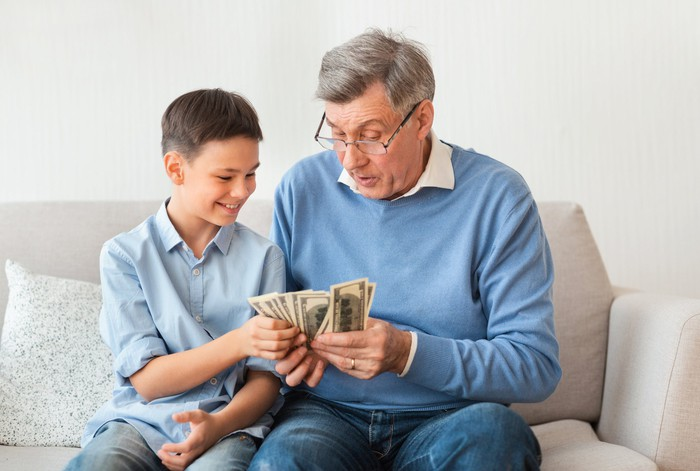 Grandad sitting on a couch counting through a wad of money with his grandson