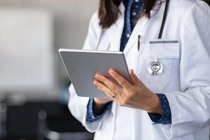 A doctor examines an iPad.