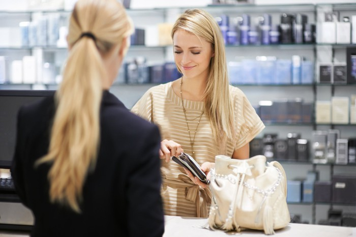 A woman helping another woman at a store with beauty products in the background.