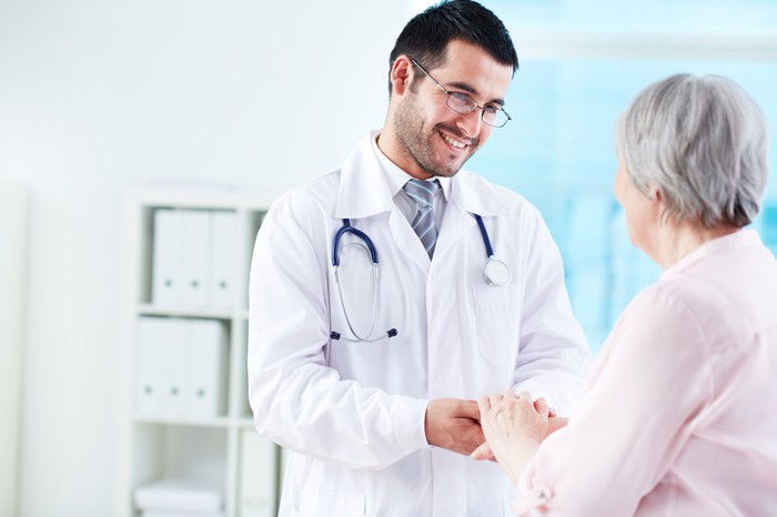 Smiling doctor holding older woman's hand