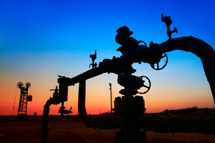 Gathering pipes near a pumpjack.