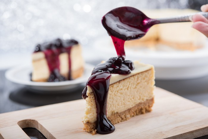 Slice of cheesecake on a cutting board with someone drizzling  a topping over the dessert.