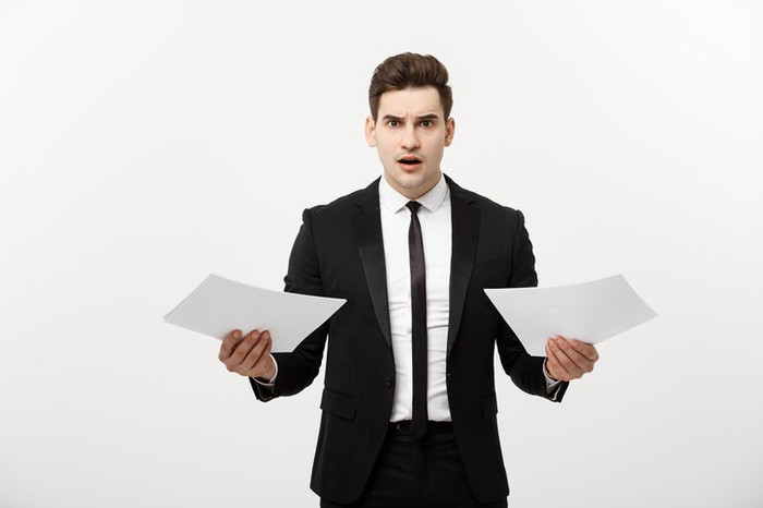A businessman with a shocked look on his face holding up papers.
