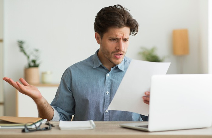 Man with shocked expression at laptop reading document