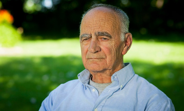 Older man with serious expression outdoors