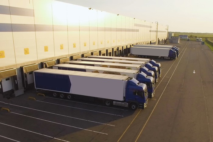 Tractor trailers lined up at a distribution center's docking doors