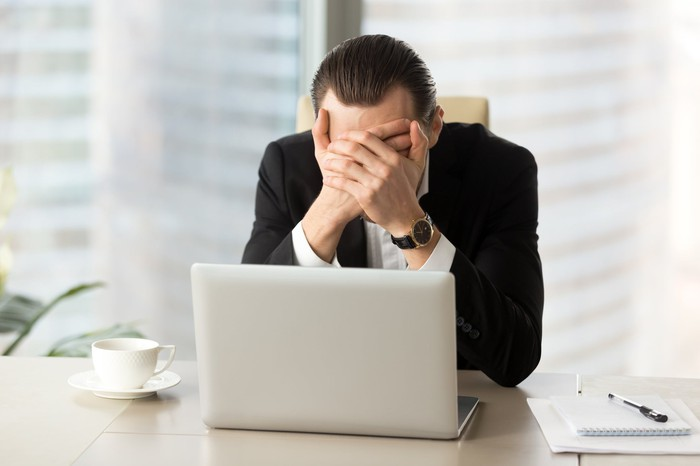 Man with hands over face in front of laptop
