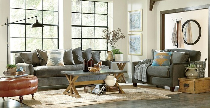 A sofa, armchair, table, ottoman, standing lamp, and other furniture arranged in a living room.