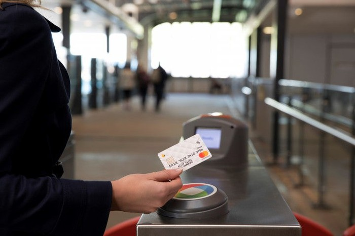 A woman using Mastercard-branded contactless pay credit card.