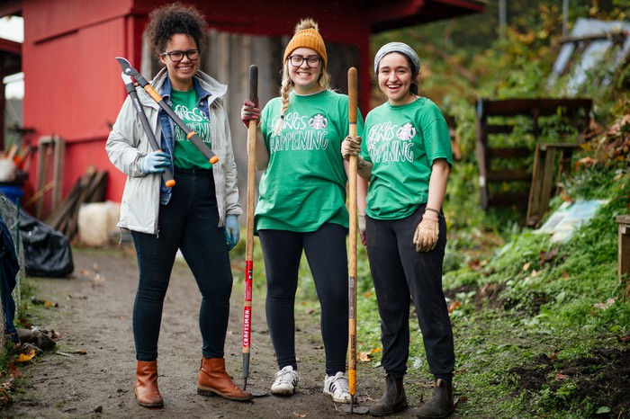 Three women wearing Starbucks' green community service t-shirts pose with agricultural tools on a farm.