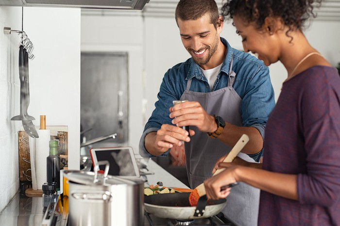 a couple cooking together over a stove