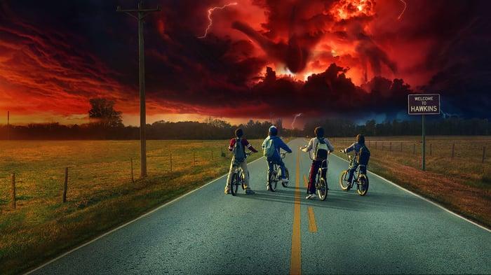 Four boys on bikes riding toward an ominous sunset.