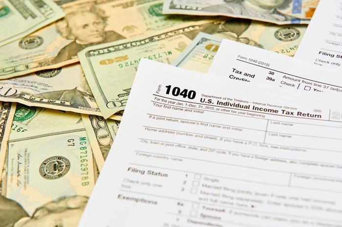 Tax Form 1040 on a pile of bills