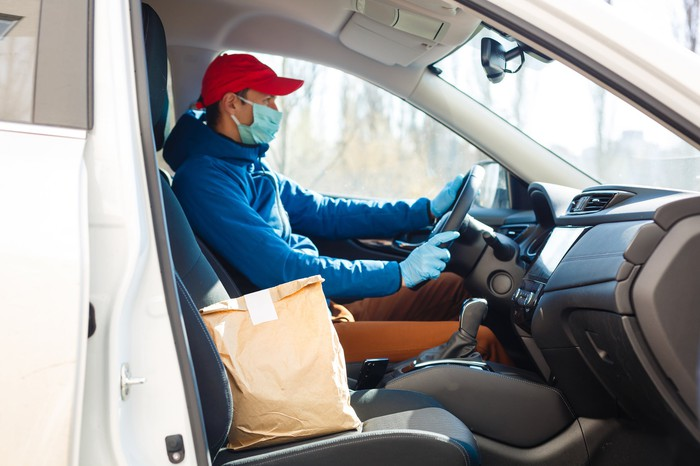 A man in a car wearing a facemask and gloves. A brown paper bag in the passenger seat.