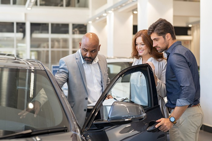 A car salesman points to a vehicle's dashboard as two prospective buyers watch