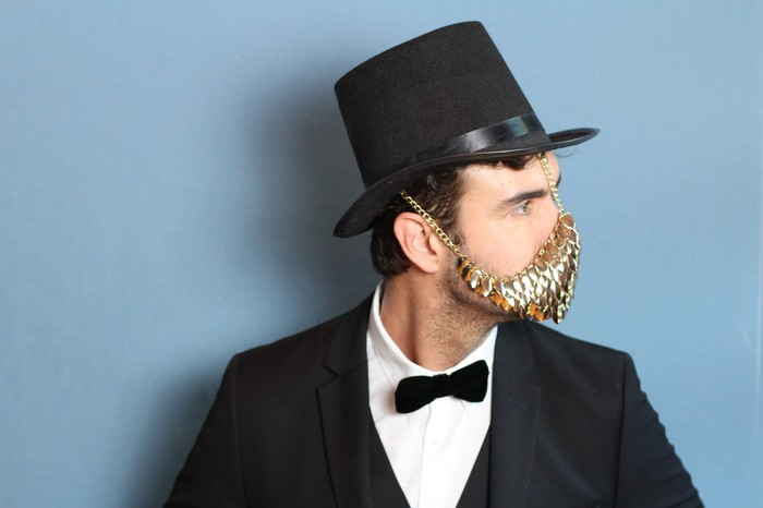 Man in tuxedo and top hat wearing a golden face mask.