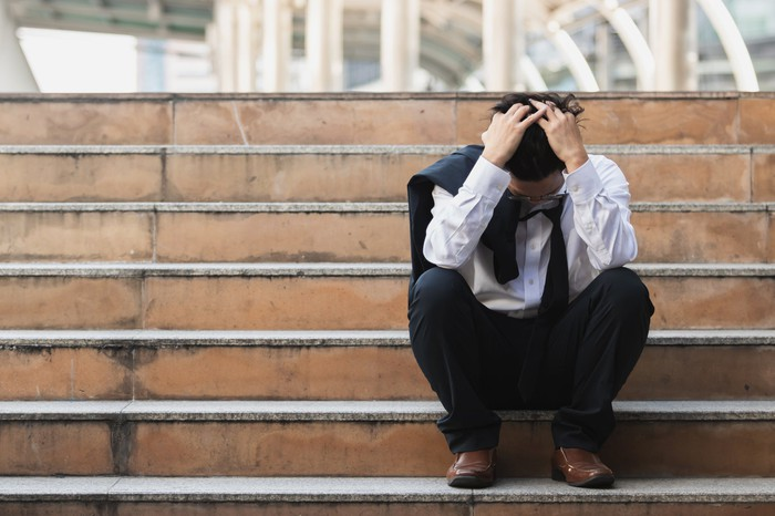 Frustrated young businessman holds his head  in his hands on the steps of an  office building.