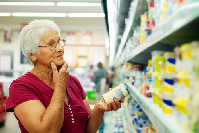 Woman holding a can of soup while standing in a grocery story aisle.